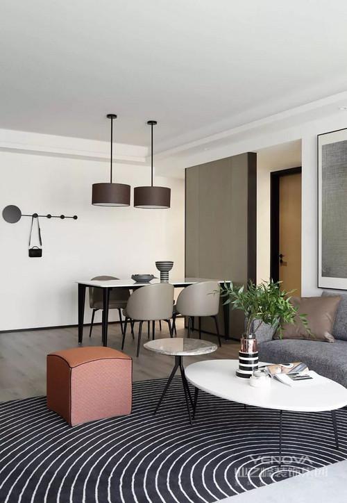 客厅、餐厅和厨房中间划分一道隔断,使整个空间形成一个完整的矩形,多出来的走廊形成了一个回字形空间,增加了许多趣味性;餐厅开放式设计,因为圆心吊灯、衣架和现代家具更为利落、稳重。
