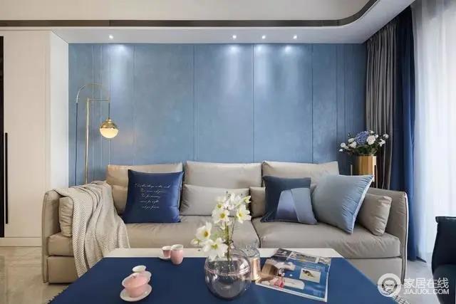 米灰色的皮沙发,上边摆着素雅的蓝色调抱枕,两侧还有铜质感的落地灯与花架,让空间显得安静而优雅华丽。