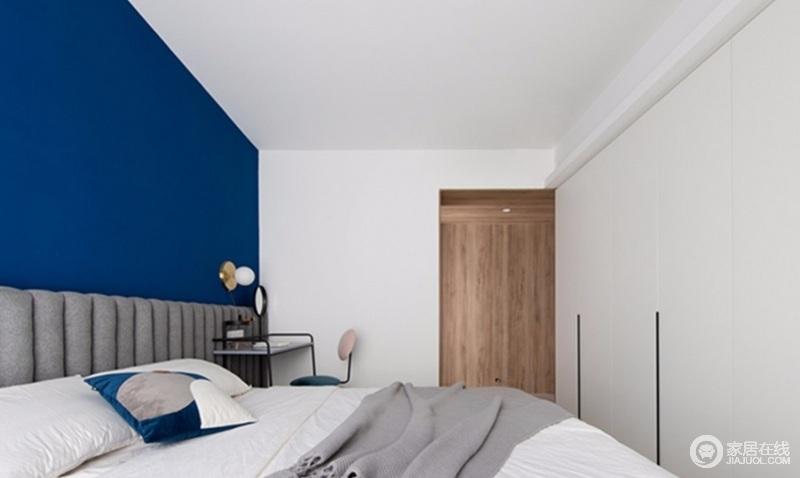 过道的木饰面就像在主卧白色的空间里,切出来的一个木盒子一样,有趣而温实;蓝色背景墙搭配灰色床头,个性的梳妆台、白色的床品,让生活简单、舒适。