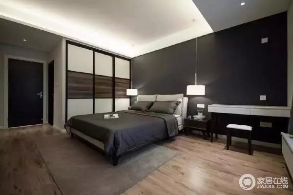 由于业主喜欢简单不失格调的摆设,主卧就没有放置很多家具,看起来主卧十分宽敞。床头背景墙刷成黑灰色,与深灰色床品正好相呼应,搭配两盏垂下来的对称吊灯,特别适合夜晚静静坐在床头看书,床头柜旁边是白色书桌,方便业主临睡前简单办公。