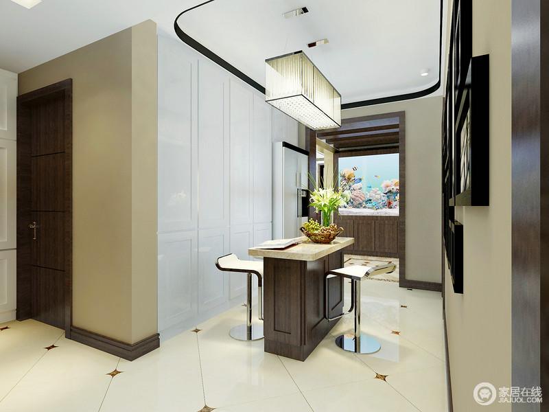 置物柜内嵌入墙,不但装饰利用墙面更能增加空间的实用性;白色置物柜和家电入墙,柜面上的线条营造,视觉上干净利落且规整有序;照片墙则作为渲染,搭配着时尚感强的吊灯,使中央吧台的休闲意味愈加浓郁。