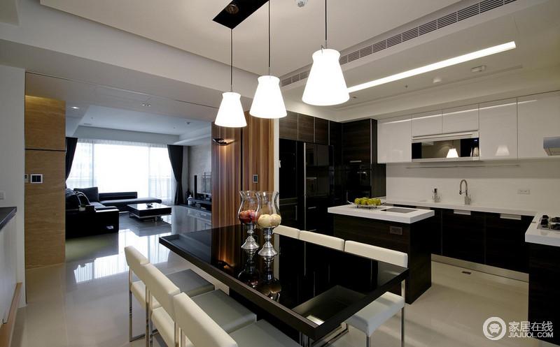 餐厅与厨房通过动线和吧台做了区分,但是依然具有互动性,只是功能分明而已;黑色玻璃门餐桌搭配白色吊灯组合、白色金属底座餐椅,呈现现代工业设计的精致和摩登。