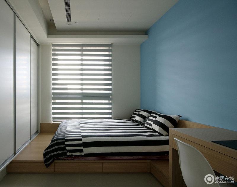 空间线条简单利落,百叶窗将光线引入空间,借百叶窗造就线性之光;白色衣柜嵌入墙体和榻榻米式的床铺形成一体,格外规整,而蓝色墙面为空间增添了不少色彩,缓解了黑白条纹床品的对比冲击,令生活氛围更为惬意。