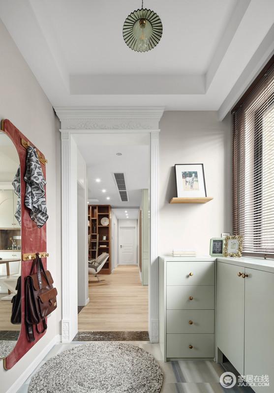 门厅的设计摆脱了原有的模式,储物柜的淡绿色,与酒红色挂毯形成冲撞,让家格外时尚;衣钩和椭圆镜子在实用的基础上,让生活颇为便利。