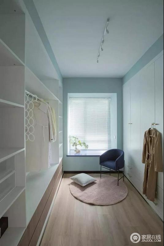 进入衣帽间,左右各有衣柜,将收纳空间彻底极致化,挂放区更是人性地解决了日常收纳;蓝色的衣柜与飘窗在藏蓝色扶手椅的陪衬中多了些许清和,