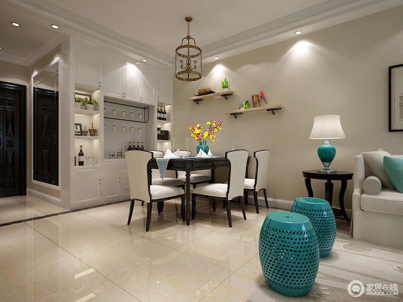 简约的餐、客厅没有明确空间划分,餐桌椅色彩鲜明,桌上宝蓝陶瓷花瓶与客厅蓝色呼应,并与笼型吊灯彰显空间的自然属性;墙面搁架与酒柜使餐厅收纳表现出多样化。