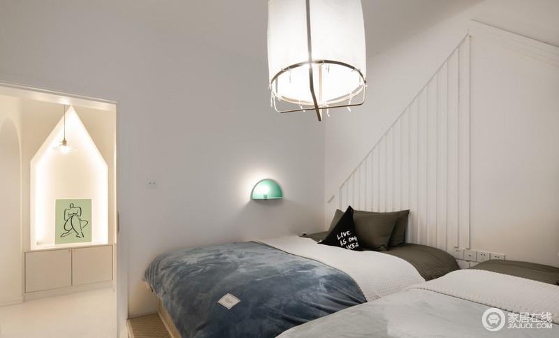 卧室以浅灰色和白色为拼接,渲染了一个素雅而静谧的氛围,藏蓝色扎染质地的床品有种庄雅,而绿色半圆形的壁灯和圆筒吊灯,给予空间光亮之外,让生活足够安适。