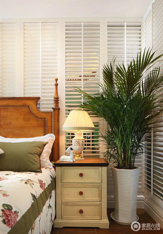 卧室的另一侧,摆放了实木床头柜、陶瓷台灯和大盆栽,绿色和白色、黄色与木色交汇在一起,真的是朴质之余,更是多了美式田园的清雅。