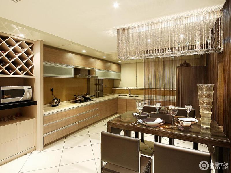 餐厨空间一体式结构足显宽敞,水晶灯给空间些许透明和璀璨之光,令实木厨柜不显得那么厚重;褐色餐桌椅组合与空间调和出了稳重,让用餐也变得更为自在、不拘束。