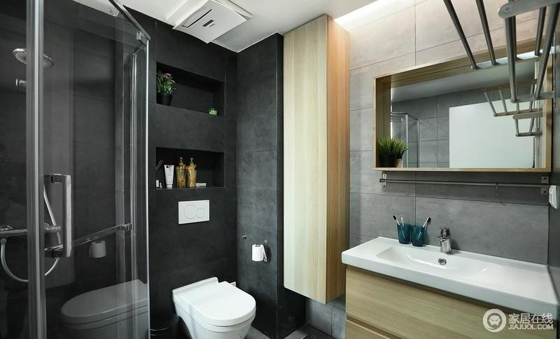 卫生间铺贴了黑色系墙砖,搭配灰色砖石,让空间更多了一些高冷,再加上干湿分离的设计,足显利落,原木盥洗柜和镜面柜颇为实用。