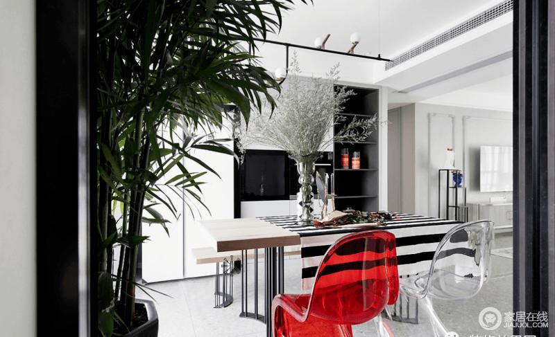 餐厅红色、白色透明质感的单椅,搭配黑白条纹的桌布,极具现代时尚感;白色餐边柜组合解决了收纳的问题,利落简洁的设计,茂盛的绿植和盛开的鲜花都让生活充满了趣意。