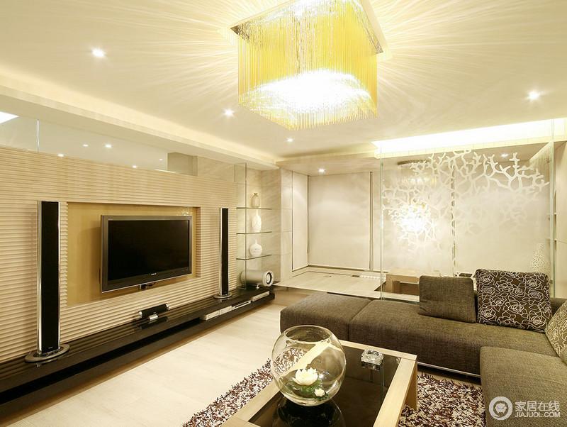 客厅以暖黄色的光来调和出温馨,而玻璃裂纹隔断将门厅与之分隔,并营造了一些通透朦胧效果;原木背景墙与灰色沙发构成反差,层次之中,成就现代利落。
