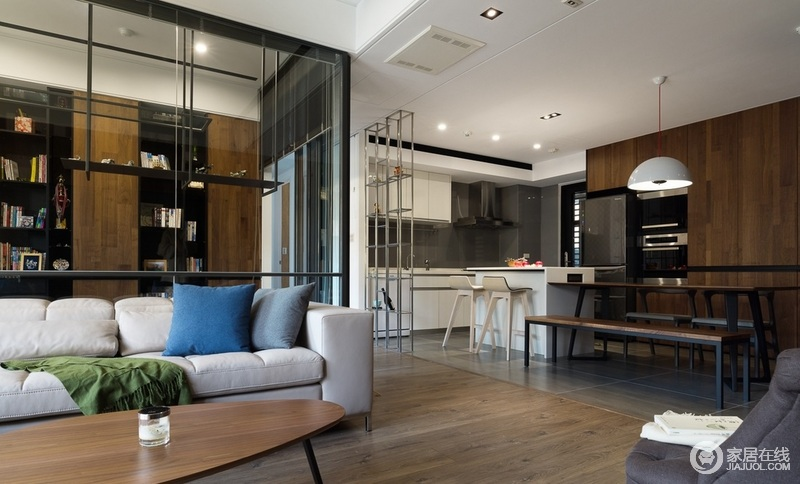 客餐厅区域没有隔断开来,使室内环境看起来宽敞开阔,互动性较强;厨房区白色的橱柜搭配灰砖,素简实用,与餐区的褐色实木座椅构成空间的不同格调,却足够精致。
