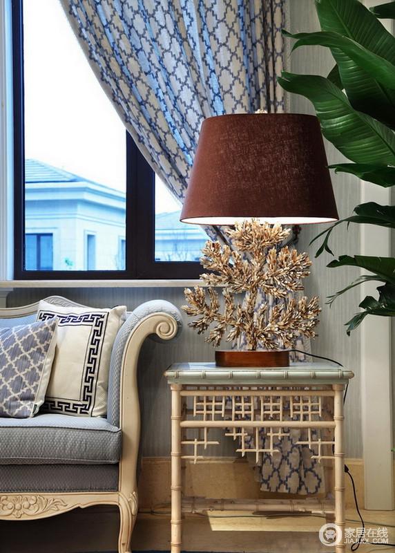 客厅的一角,蓝色沙发和暗红色的台灯,因为花植和家具更为清和与唯美。