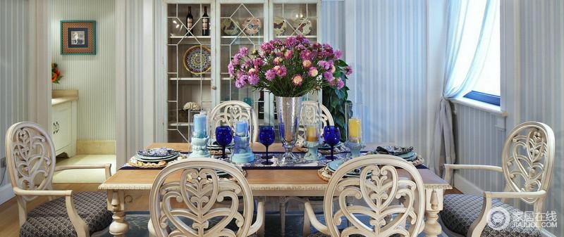 餐厅的中央永远是餐桌,紫色花卉与蓝色系酒杯、烛台构成色彩感,激活了空间的色彩能量;铁艺收纳柜陈列着艺术品,与浅蓝色条纹壁纸及窗帘,构成地中海的清风雅致。