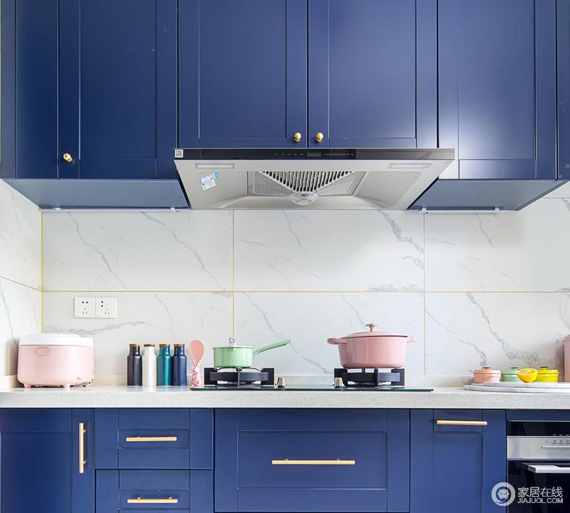 厨房选用灰白色的墙砖来铺贴立面,而橱柜的藏蓝色装饰出空间的摩登,搭配金色五金件,足够让空间实用、轻奢。