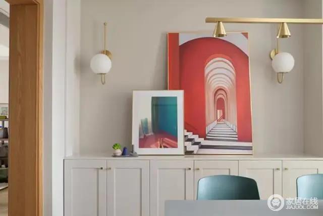 餐边柜矮柜的台面上,摆了几幅色彩强烈且立体感明显的装饰画,结合墙面的金属壁灯,让用餐氛围更加时尚活跃。