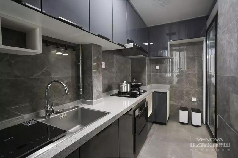厨房内部的橱柜延续了客餐厅的柜子颜色,深灰色的大理石墙砖搭配灰色的哑光地砖,整个厨房看起来很有现代感。