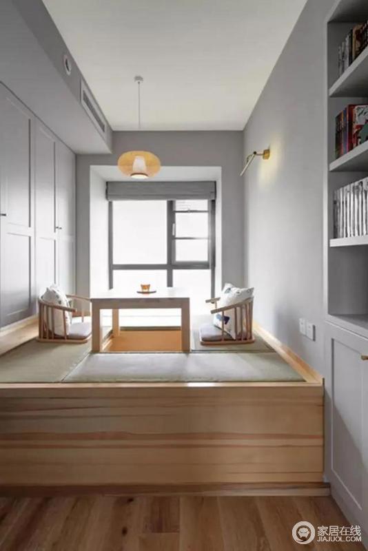 木质定制榻榻米柜中间的升降台区域,让这个榻榻米房成为家人休闲喝茶或聊天的好空间;在灰色的墙面空间,侧边的定制柜与书架也是以灰色,整体空间显得简约而又自然。