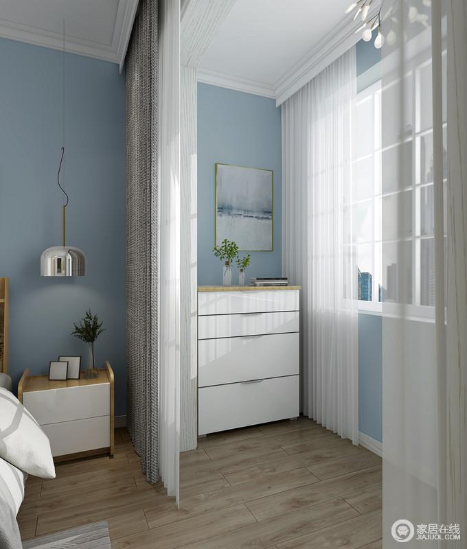 阳台区和休息区通过灰色和白色纱幔简单分隔,也起到遮挡的作用,蓝色漆的墙面作为底色,营造了一个轻快的生活氛围。