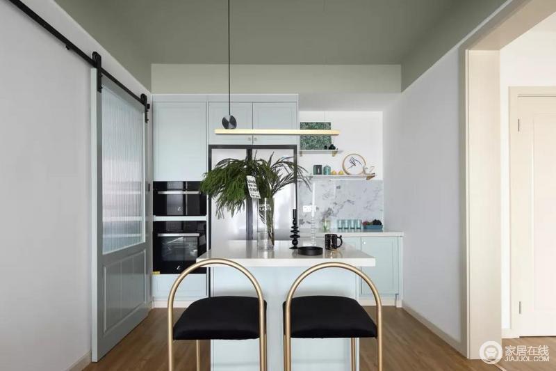 餐厅和客厅相对,餐桌用一个岛台来代替,在餐厅的边上做西厨的设计,微波炉、冰箱等电器被嵌入到了柜子当中,增加了实用性;青蓝色的柜子带来一些清新感,与黄铜餐椅和绿植,让生活足够有格调。