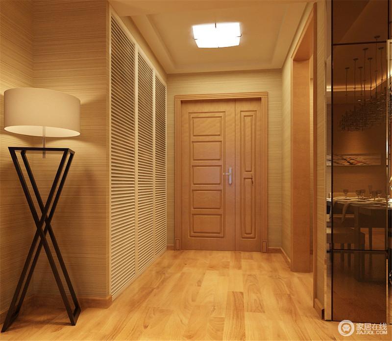 门厅开阔而宽敞,设计师因势导利的将收纳柜入墙,用百叶门的线条与墙面壁纸的细腻肌理,和谐规整的融合一体,看上去舒适大方且功能实用;角落映照的双叉实木落地灯,支架色调与深色玻璃对称,视觉上显得和谐庄重。