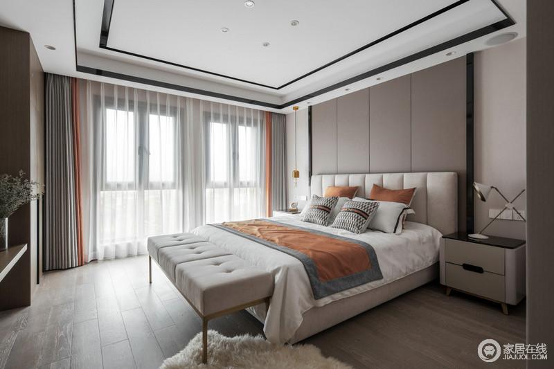 卧室因纱幔多了些许缥缈,让原本成熟中性调的空间多了轻快;床头背景墙为定制的高颜值皮质硬包,在床头柜的台灯映衬下扩展了空间既视感,橙色布艺点缀,搭配现代古典床尾凳,让生活也多了一份轻奢之调。