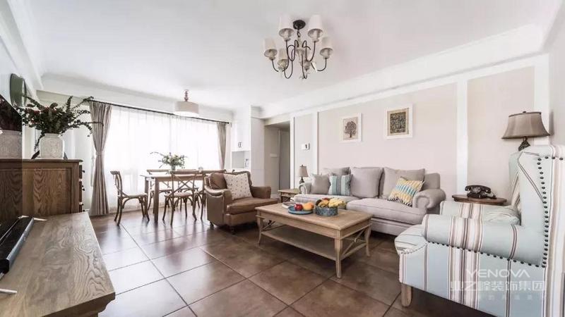 客厅地面通铺复古地砖,墙面刷成浅米色,简约的顶面装一盏美式吊灯。