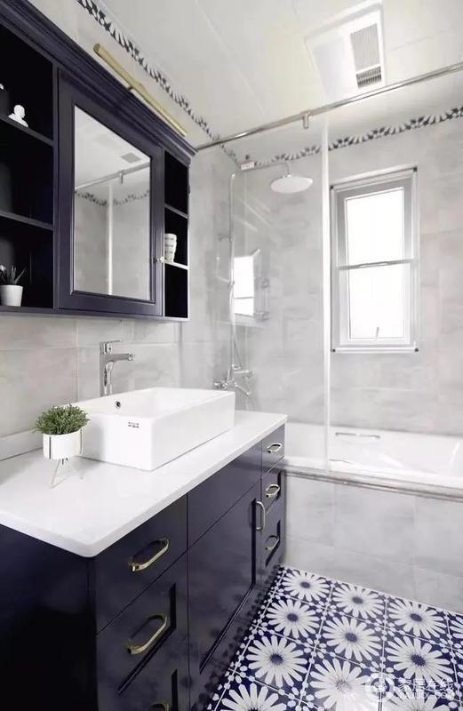 主卫浅灰色的复古墙砖搭配落地烤漆台盆柜,结合美式镜柜,地面搭配深蓝花砖,色调中氤氲着冷冽的气质,柔和的触感彰显空间优雅本色。