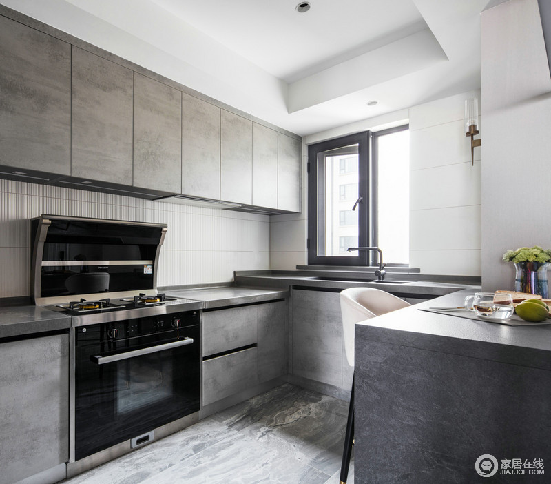 整个厨房因为大理石地砖的肌理,让空间多了天然的淳朴,与整洁地线条构成现代工业时尚;仿岩板材质吧台延续了厨房的灰调,同时与深灰色木纹橱柜组合得天衣无缝,随手就能拿到所用的餐盘和器物,增加了屋主用餐的便捷度,为隔壁的开放式厨房增添生活趣味。
