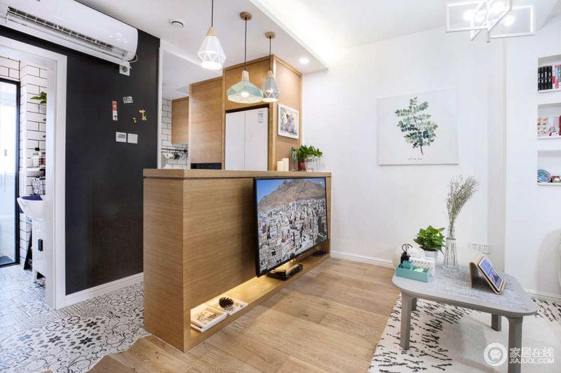 设计师很巧妙的将吧台与电视柜结合,原木的材质清新的延展至开放式厨房,让空间的休闲感兼有划分区域的功能。