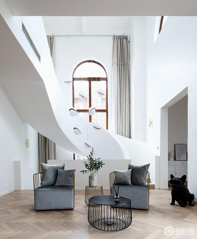 整个空间因为挑高带来强烈的光线感,曲线楼梯与拱形窗,呈现着建筑设计的艺术感,灯具点缀期间,调和出精致;灰蓝色扶手椅组合以竹子为材料,搭配绿植,带来一种自然般的和谐,也不失时尚。