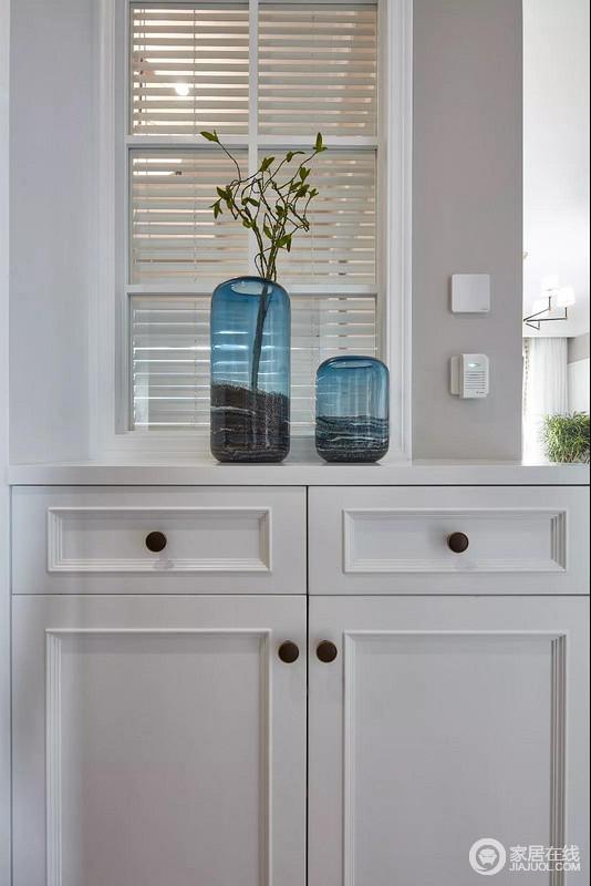 门厅的矮柜后有个室内窗,,以百叶帘作为窗帘,透而不空的视觉感,非常的优雅端庄;白色的边柜搭配白色玻璃花瓶,给予空间一丝清雅静美。