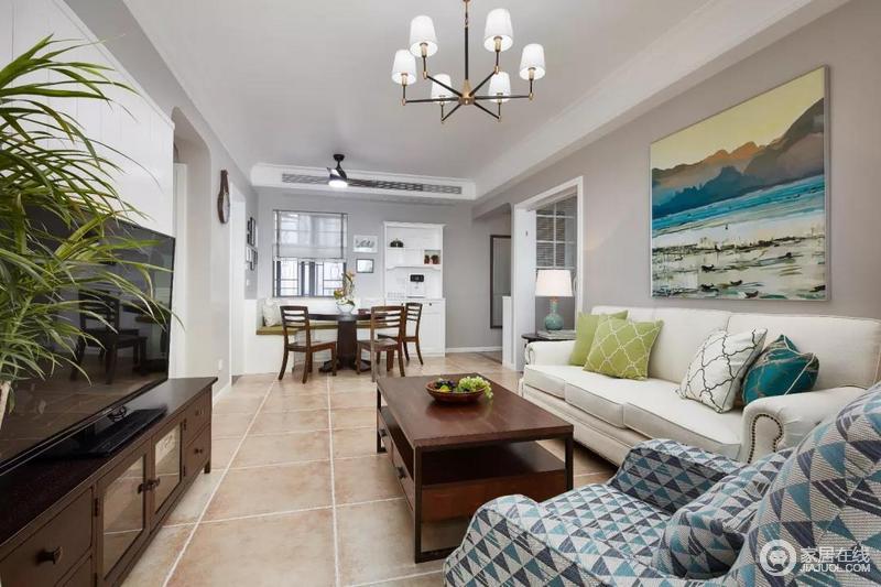 """整个客厅以简单大方的现代美式为主,从电视墙与沙发墙也秉承了""""简单""""的章法,一幅风景画装饰出田园之意;乳白色现代美式沙发上青绿色和白色菱形靠垫,搭配上蓝色几何美式单人沙发,构成一个和谐的休息区,给现代美式的空间带来一份端庄。"""
