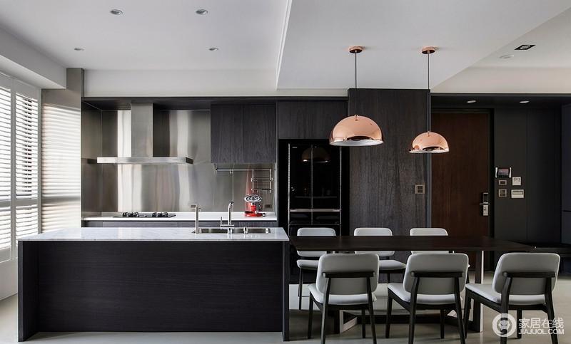 厨房金属板材的墙面搭配黑色橱柜,太色台面与之融合为一,简洁实用,正如岛台的设计一样,足够让厨房生活简单、利落;北欧金属灯和灰色餐椅让生活多了份时尚,给予主人一个美好的用餐时刻。