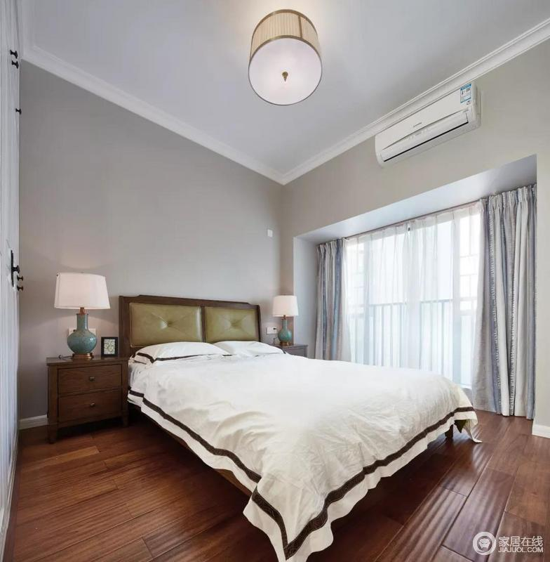 """卧室的天花板四周装上石膏线,与暖灰色墙面、胡桃木地板以""""块状""""的设计,形成整洁利落;美式家具和台灯搭配白色床单,显得端庄而又雅致。"""