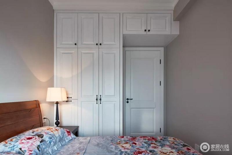 卧室进门后,顶部空间也跟衣柜连贯起来装成收纳柜,增加了储物空间;而大幅鲜花图案的床单,也为这个沉稳的空间添加了几分花样之语。