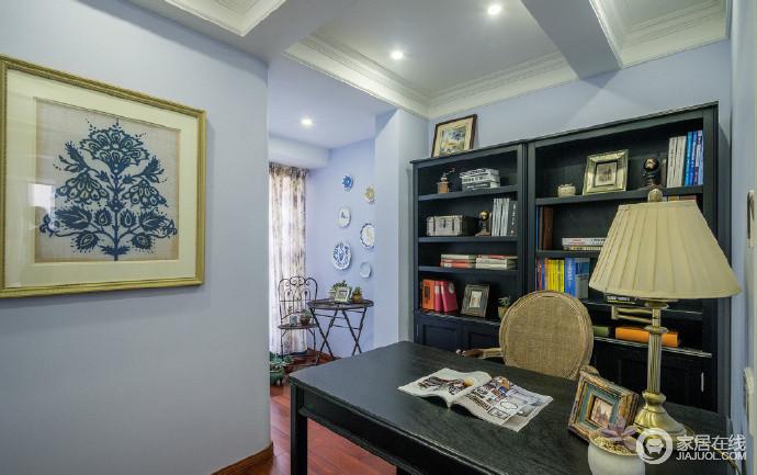 空间以淡紫色漆粉刷空间,营造一种梦幻,黑色书柜与书桌成套配置,收纳与实用,让生活格外轻松;阳台处墙面的餐盘装饰点缀出美式田园的清和与自在,锦上添花,也不会让书房过于压抑。
