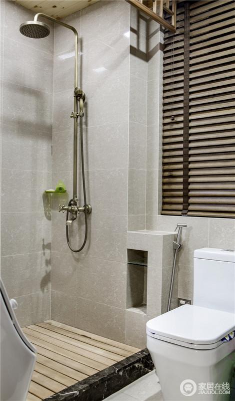 """卫生间简单地通过防腐木来避免淋浴房打滑,通过与实木百叶窗形成呼应,让空间多了几何之美;浅灰色砖石让整个空间格外利落硬朗,可谓""""小空间、大舒适""""。"""