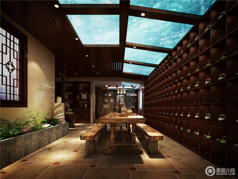 茶室将吊顶做成了海底世界般的效果,并借灯光系统对空间做了调节,让室内随着室外而变;地板选用了伊莫拉陶瓷瓷砖,在使用过程中不会磨损,反而地板越来越光滑平整,同时,几何的拼接效果,让地面更显个性;原木茶桌和长条凳打造了一个恍如回归原始的感觉,让人更能放松下来,整排墙陈列了茶器木柜,气势恢宏,而书柜的设置,调剂出生活的温情,也凸显了主人的品味。