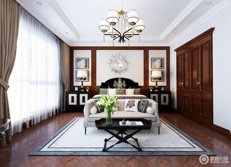 空间白色吊顶以线条勾勒大气,与胡桃色波纹地板形成色彩和动静之美;背景墙胡桃色板材几何结构基础上,张贴了金属饰品和挂画,成就对称美学;现代风的灰色床头柜简洁大气,搭配休息区的黑色边几,尽显实用哲学,再加上中性色的软装布艺,赋予空间更多的温馨。