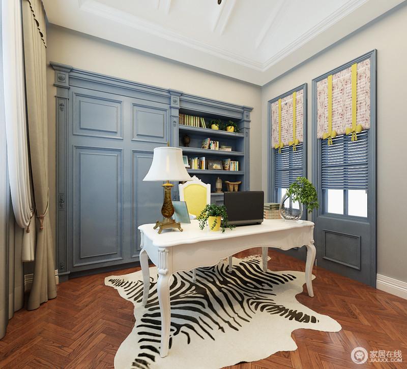 空间白色吊顶与驼灰色立面勾勒了素静,搭配白色脚线更显利落;书柜作了嵌入式设计,搭配门窗,构成古典建筑之美,再加上蓝色的色调调和出了雅致,与白色古典风的书桌构成空间的清和、华美,黑白条纹地毯注入了些许俏皮。