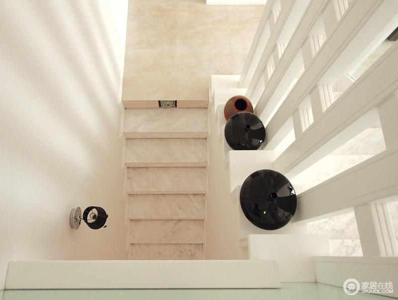 从下俯瞰整个楼梯,楼梯台阶以大理石材来作铺贴,硬朗之中,雕刻着朴质;栏杆的结构既简单区分空间,也凸显了结构之美。