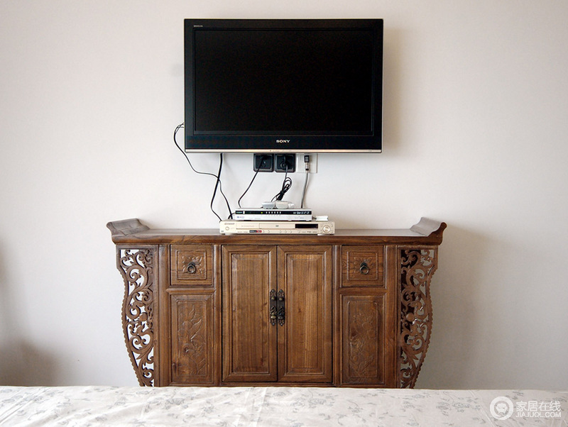 卧室设计上十分简单,以白墙为主,搭配素色碎花床品,营造素雅的氛围,而实木电视柜的中式复古风,足显尊贵,让生活多了东方厚泽。
