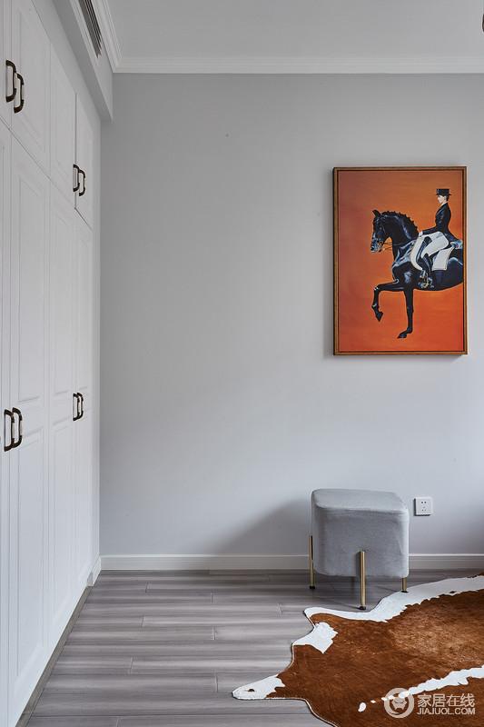 衣帽间以功能为主,灰色的墙面让空间变得简单静谧;白色定制得衣柜收纳性十足,橙色底的骑士画作多了户外野性的奔放,灰色小椅便可偷得浮生半日闲。