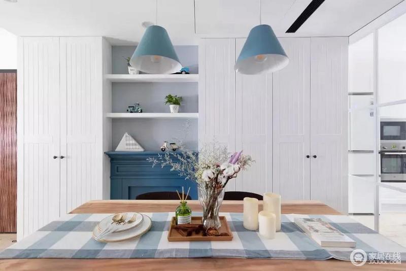 餐厅区域专门打造了一整面墙的餐边柜,中间蓝色的壁炉十分抢眼,实用又美观,与蓝色吊灯构成呼应。