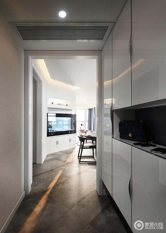 门厅空间较为狭长,白色定制储物柜解决了收纳问题,让空间足够利落;褐色木地板的古朴,与之形成现代大气,出入也便捷。