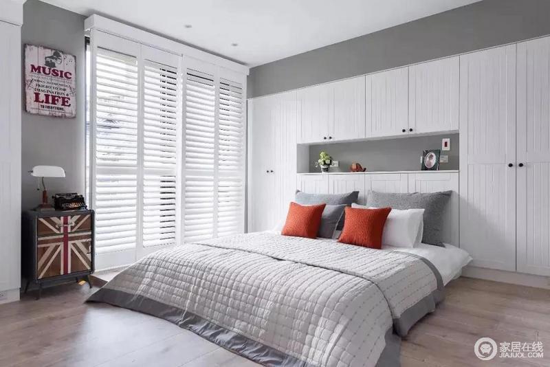 主卧床头打造了一整面墙的收纳柜,收纳功能十分强大,大大的落地窗使得空间光感充足;整体以白色为主色,灰色和红色靠垫做点缀,干净舒适之余,多了生活的新鲜度。