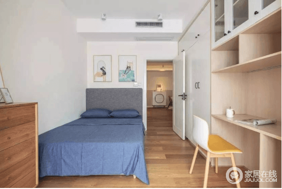 次卧则是用一整面墙的定制依归作为收纳,让空间具有功能性,还不失空间性;为了将死角空间利用起来,设计师选择将木床放在靠角一侧,藏蓝色的床品搭配彩色挂画,给空间带来庄重之余,也填活力。