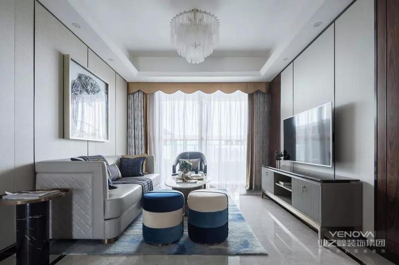 米白色调为主的客厅,地毯与小圆凳加入淡雅的蓝色调,电视墙与沙发墙都以硬包护墙板为背景,整体现代温馨又雅静的布置,给人以轻松舒适的浪漫氛围感。